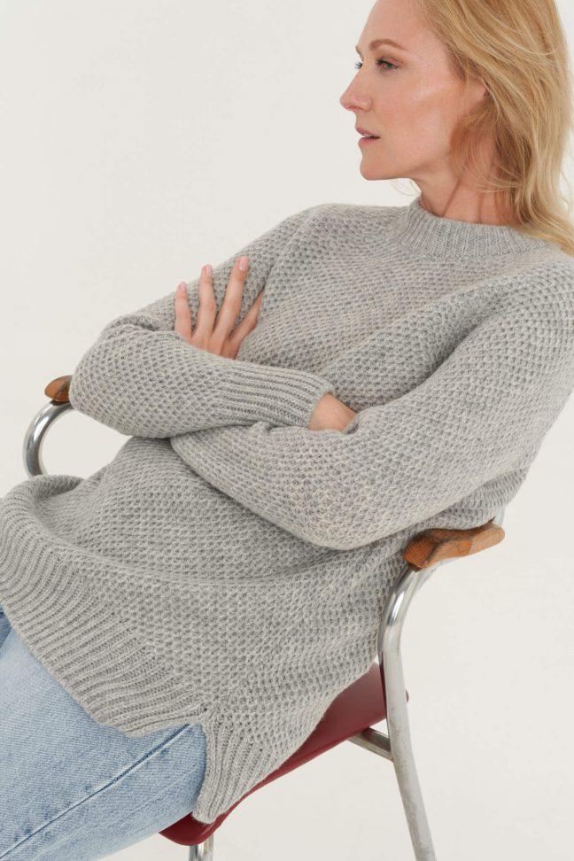 šviesiai pilkas megztinis koriuko raštu